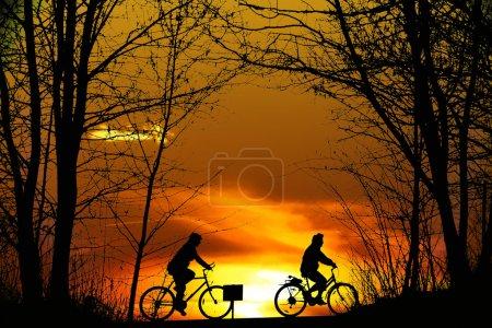 Photo pour Deux silhouette de VTT au coucher du soleil - image libre de droit