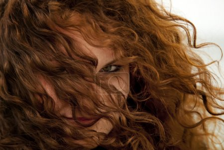 Close-up view in eye of curly red-haired girl.