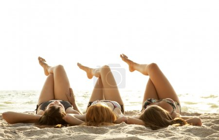 Three beautiful young girlfriends in bikini on the beach at sunr