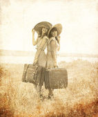 Two retro style girls with suitcases at countryside.