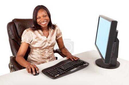Photo pour Femme d'affaires afro-américaine souriante travaillant à son ordinateur - image libre de droit