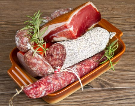 Photo for A composition of different sorts of cold cuts on wooden table - Royalty Free Image