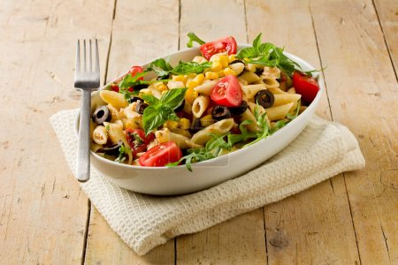 Photo for Photo of delicious tasty pasta salad on wooden table with fresh vegetables - Royalty Free Image