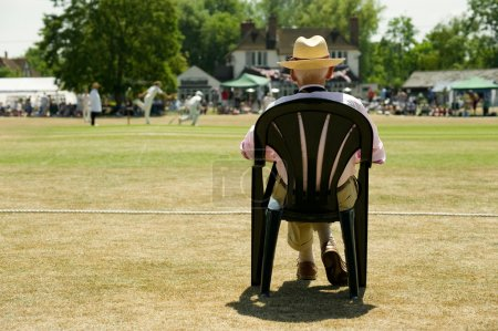 Photo for Senior man watching a game of cricket on a picturesque English village green on a bright summers day. - Royalty Free Image