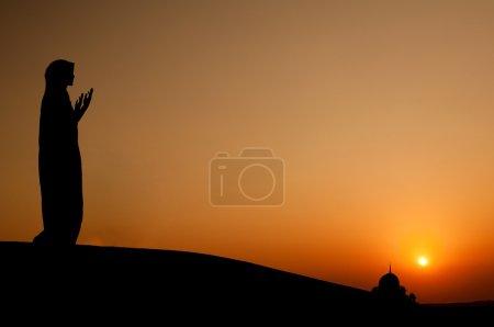 Photo pour Silhouette d'une femme musulmane de prier sur le désert - image libre de droit