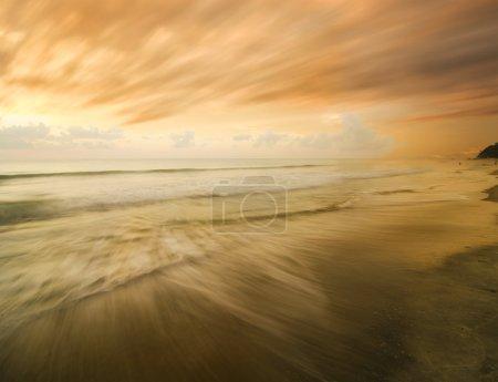 Photo pour Nuages rapides au coucher du soleil sur la plage - image libre de droit