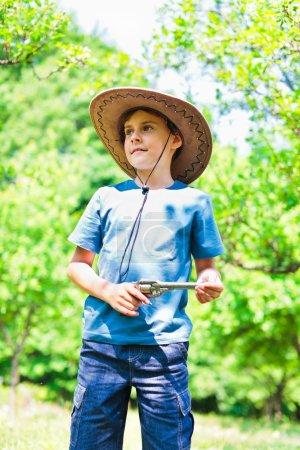 Photo pour Portrait d'un garçon mignon avec chapeau de cow-boy en plein air - image libre de droit