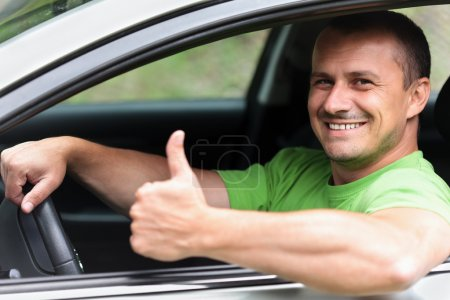 Happy young man with new car
