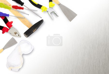 Photo for Different tools - hammer, plyers, screwdrivers,spatula, paint roller on metal surface with copyspace - Royalty Free Image