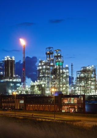 Photo pour Usine pétrochimique éclairée au crépuscule (port d'Anvers, Belgique) ) - image libre de droit
