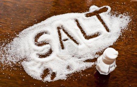 Foto de Escrito en mostrador de sales derramadas sal - Imagen libre de derechos