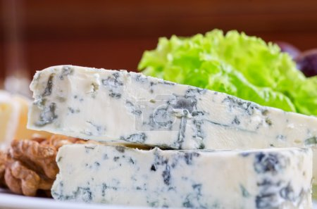 Blue cheese with lettuce, grapes and nuts closeup...