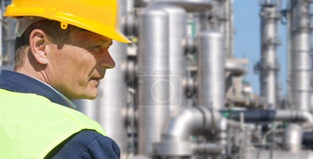 Photo for Close up of an engineer wearing a safety vest, blue coveralls, and a hard hat in front of a petrochemical plant - Royalty Free Image