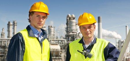 Photo pour Deux ingénieurs pétrochimistes devant une raffinerie, vêtus de casquettes et de gilets de sécurité - image libre de droit