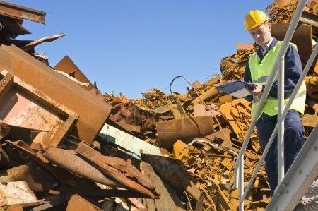Photo pour Recyclage expert, debout sur un escalier en métal devant un tas de ferraille en acier - image libre de droit
