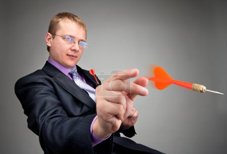 Businessman throwing red dart