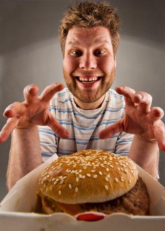 Happy man preparing to eat burger