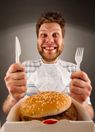 Photo for Portrait of happy man with knife and fork ready to eat burger - Royalty Free Image