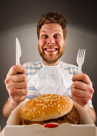 Photo pour Portrait d'un homme heureux avec couteau et fourchette prêt à manger des hamburger - image libre de droit