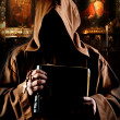 Portrait of medieval monk with bible in church...