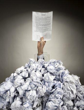 Photo pour Main avec accord tend la main de gros tas de papiers froissés - image libre de droit
