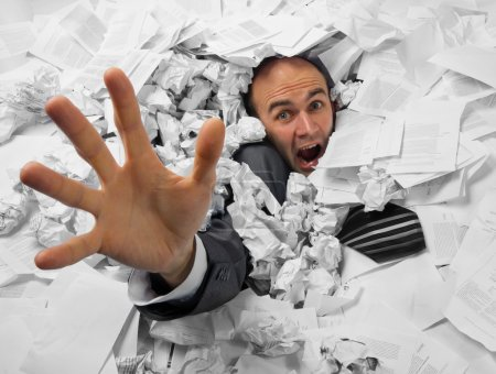Businessman sinking in heap of documents and askin...