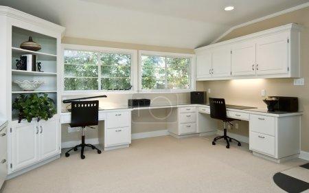 Photo pour Grand espace bureau à domicile, trois espaces de travail avec armoires et étagères à livres, deux grandes fenêtres - image libre de droit