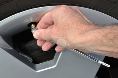 Checking the Air Pressure of a Tire with a Tire-Pr...