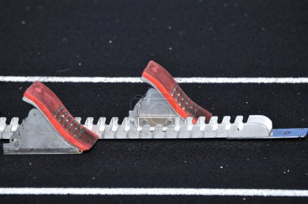 Photo for Empty Starting Blocks on a Black Track - Royalty Free Image