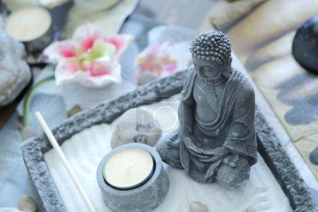 Photo pour Bouddha en face d'une petite bougie jaune sur un zen table pierre grise - image libre de droit