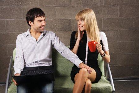 Photo pour Jeune homme et femme assis avec un ordinateur portable à l'intérieur - image libre de droit