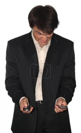 Angry businessman holding two mobile phones