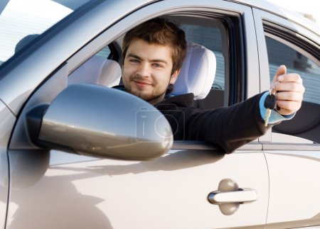 Photo for Young man driving his new car, holding out keys - Royalty Free Image