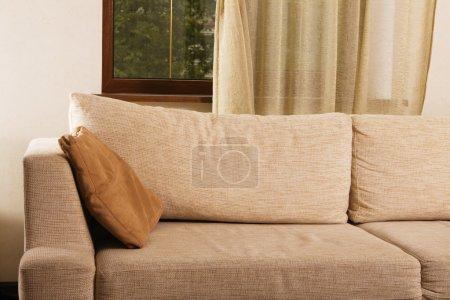 Beige comfortable sofa in home interior