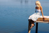 Girl sitting on a pier at the river bank