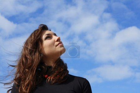 Beautiful young woman looking into the sky