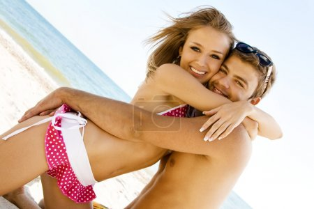 Young cheerful couple having fun on the beach