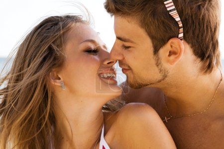 Young beautiful couple kissing on the seaside