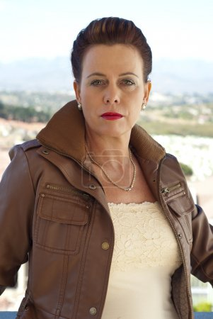 Stylish older woman in brown leather jacket