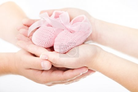 Mother's and father's hands holding pink newborn baby booties. O