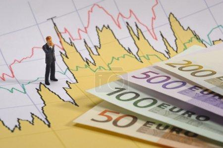 Photo pour Homme d'affaires sur le tableau de bord financier avec billets en euros - image libre de droit