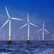 White wind turbine generating electricity on sea...