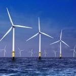 White wind turbine generating electricity on sea...