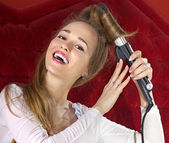 Young girl curling her hair