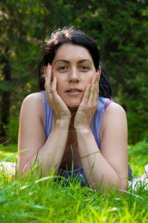 Photo pour Belle femme d'âge moyen allongée sur l'herbe - image libre de droit
