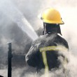 Fireman spraying water in a smouldering burnt out ...