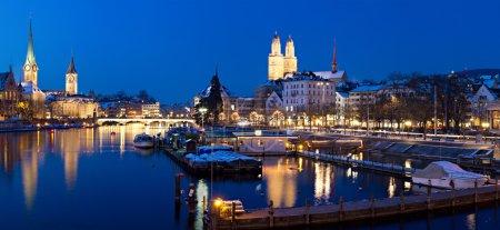Photo pour Panorama: zurich, centre fanancial suisse vu de la rivière Limmat dans la nuit avec le centre-ville historique et ses églises reflétant dans le flux - image libre de droit