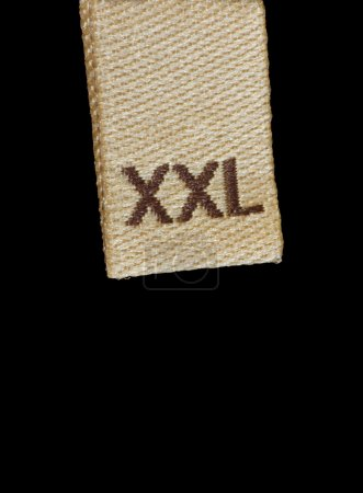 Macro of XXL size clothing label, large closeup isolated on black