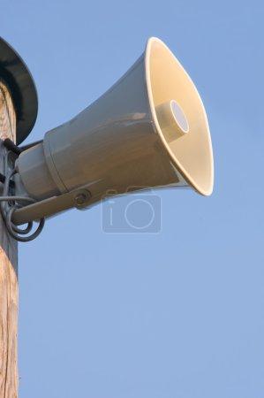 Light grey horn loudspeaker on the pole over blue sky