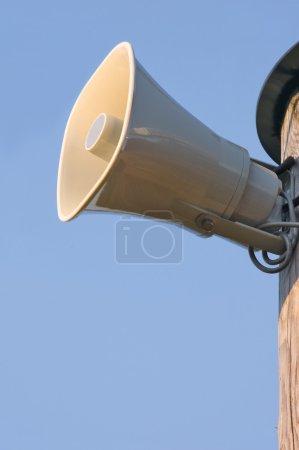 Grey horn loudspeaker on the pole over blue sky